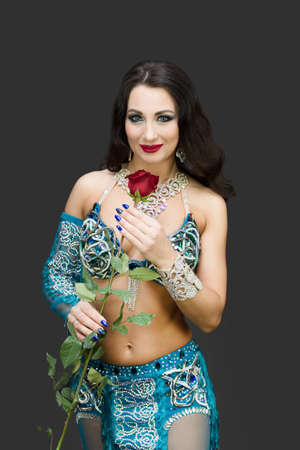 Brunette woman in blue clothes holding a flower near her face.