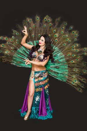 National dancer in a luxurious outfit of bird feathers on black background, isolated.