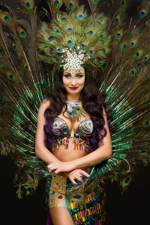 Brunette woman with feathers on her head against the background of lush peacock feathers.