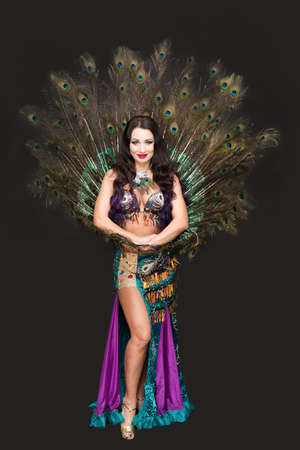 Brunette woman with loose hair on background of lush peacock feathers.
