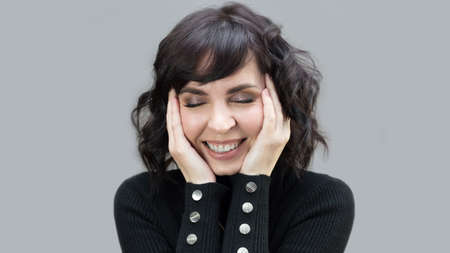 Happy adult woman closed eyes and laughs on gray background.