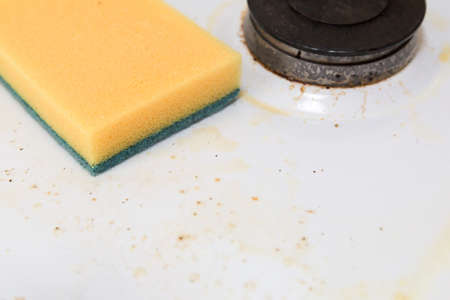 Cleaning sponge on the surface of a dirty gas stove. Close-up