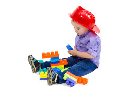 Boy in a firefighter's helmet sits on floor playing with toys.