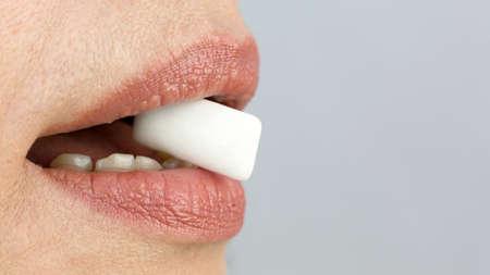 Pad of chewing gum between teeth, close-up. 版權商用圖片