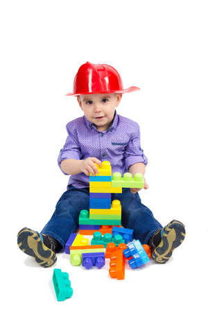 Boy in a firefighter's helmet sits on the floor playing with toys.