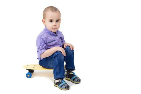 Boy sitting on skateboard isolated white background.