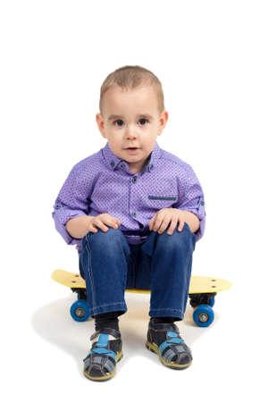 Boy sitting on skateboard, isolated white background.
