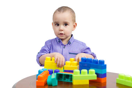 Kid playing with colored cubes on the table, isolated. 版權商用圖片
