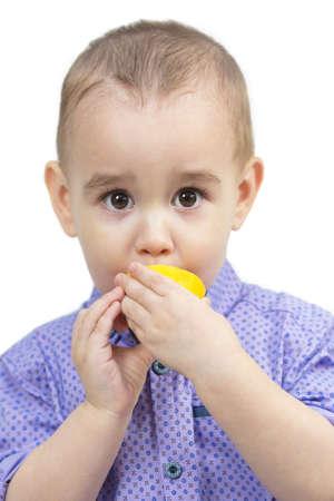 Little boy bites juicy sour lemon white background.