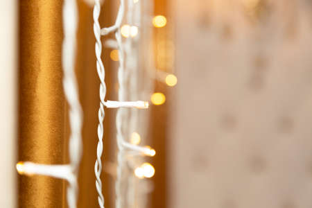 Garland lights are burning near the wall on a brown background, bokeh.