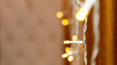 Garland lights are burning near the wall on a brown background, bokeh. copy space 版權商用圖片