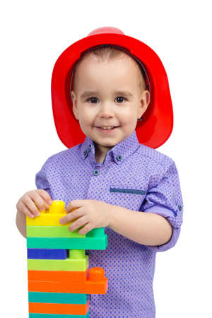 Funny boy with a bunch of toys in his hands, white background ashed.