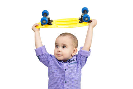 Little boy holding skateboard above his head, white background.