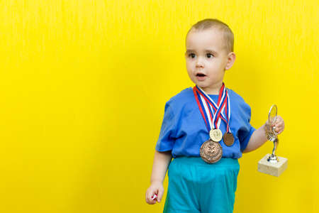 Surprised boy with sports awards on yellow background. Copy space