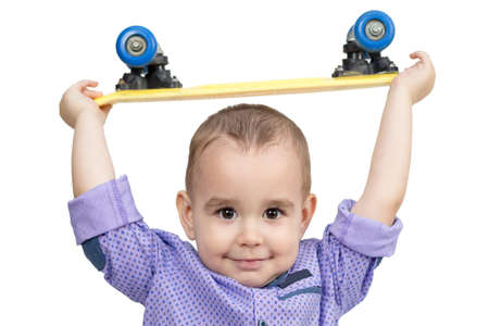 Little boy holding a skateboard above his head, white background.