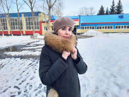 A woman in winter clothes stands in the snow near a city school.