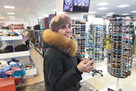 Woman in winter clothes smiling in the trading floor of the store.