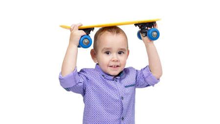 Little boy holding a skateboard above his head white background. 版權商用圖片