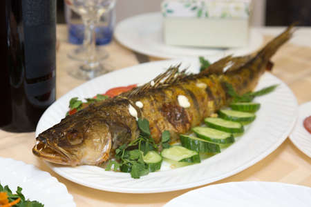 Large fried fish on a platter with vegetables and herbs.
