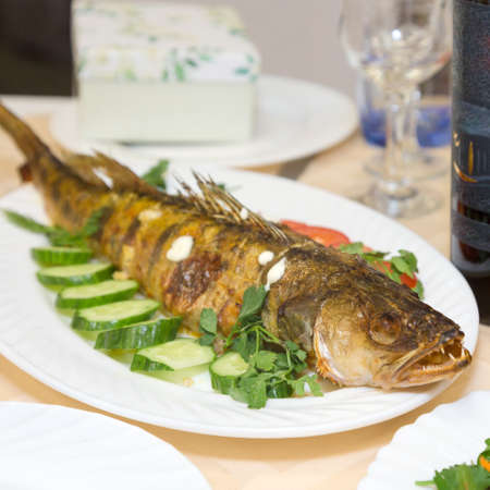 Large fried fish on platter with vegetables and herbs.
