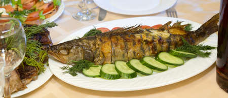 Large fried fish on a platter with vegetables and herbs.,