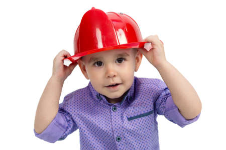 Boy with hands holds a hard hat on his head, isolate white background.