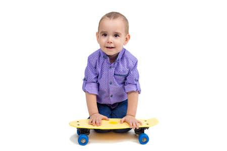 Child sitting on floor with skateboard isolated. 版權商用圖片