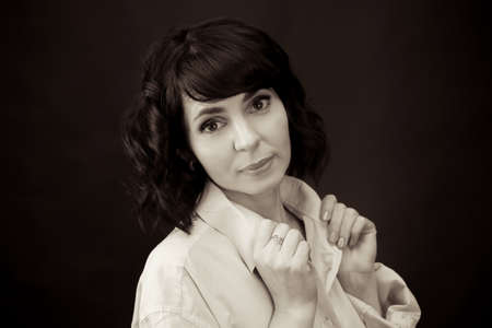 Adult woman in a men's white shirt with black hair. Black and white image