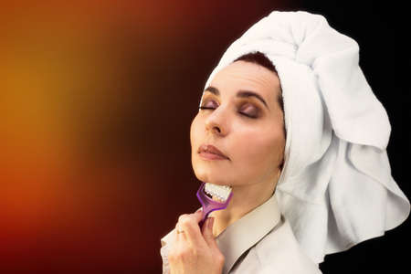 Woman smoothes the skin on the face from wrinkles with a massager, copy space.