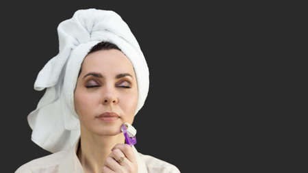 Woman smoothes the skin on the face from wrinkles with a massager copy space
