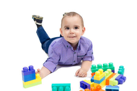 Boy lying on the floor with toys, isolated white background.