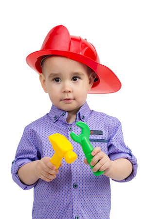 Child 3 years old in helmet with construction tools in hands. 版權商用圖片