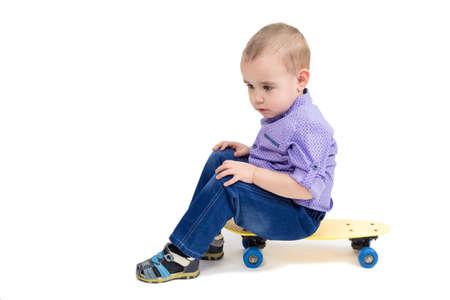 Sad child sitting on a skateboard, tired and sleepy.