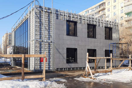 Facing a building under construction with square panels.,