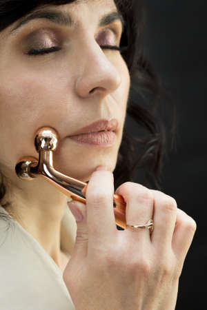 Brunette woman doing facial massage with small massager.,