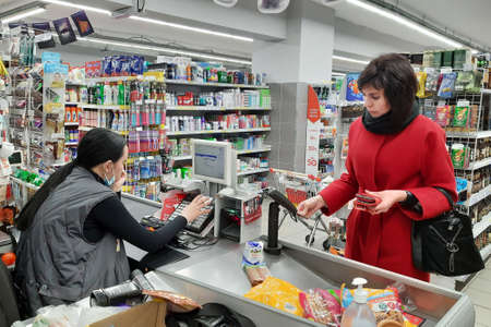 Yasny town, Russia - April 11, 2021 Woman shopper at the checkout of the store, editorial Woman shopper at the checkout of the store pays with a plastic card. editorial