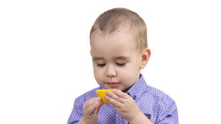 Preschool boy eating sour lemon isolated white background. 版權商用圖片