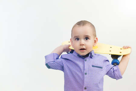 Preschool boy with skateboard on shoulder isolated white background. 版權商用圖片