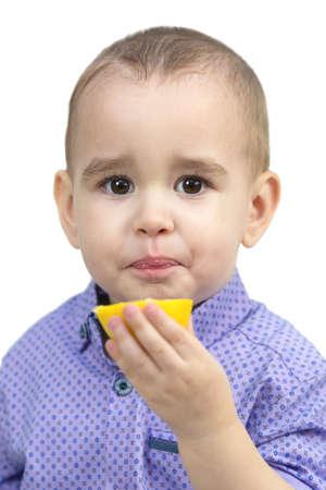 Preschool boy eating sour lemon, isolated white background. 版權商用圖片