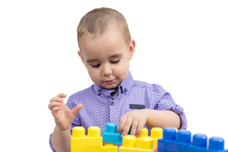 Preschool boy playing with cubes isolated white background.