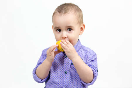 Caucasian boy 3 years old eating lemon on white background.