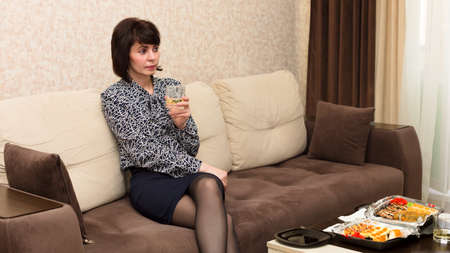 Woman bored at home at table with glass of white wine, loneliness concept. Banque d'images