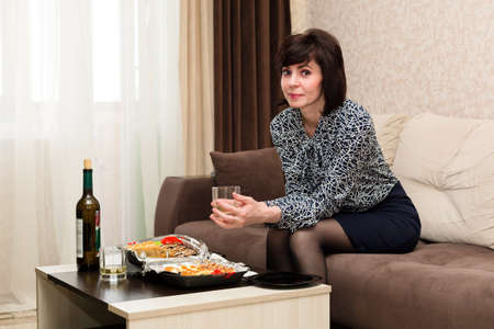 Woman bored at home at table with glass of white wine loneliness concept. Banque d'images