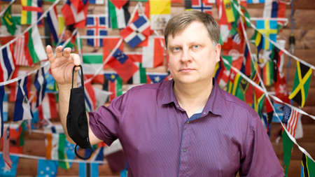 A man shares a used medical mask in his hands against the background of country flags.