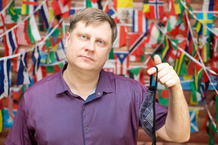 A man shares a used medical mask in his hands against background of country flags.