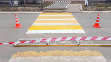 Painting repair of pedestrian crossing lanes across the road.