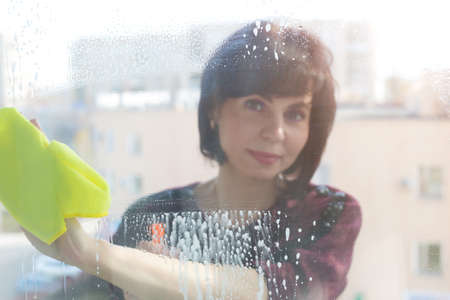 Woman housewife washes window, wipes foam on glass. Blurred image, no focus