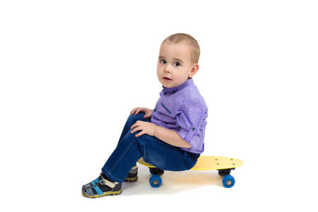 Three year old boy in jeans sits on a skateboard. Isolated. Banque d'images