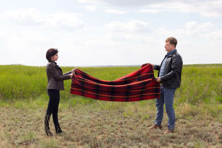 Man and woman lay a blanket on the ground for a picnic in nature. Banque d'images