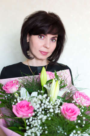 Adult woman with large bouquet of flowers in her hands.